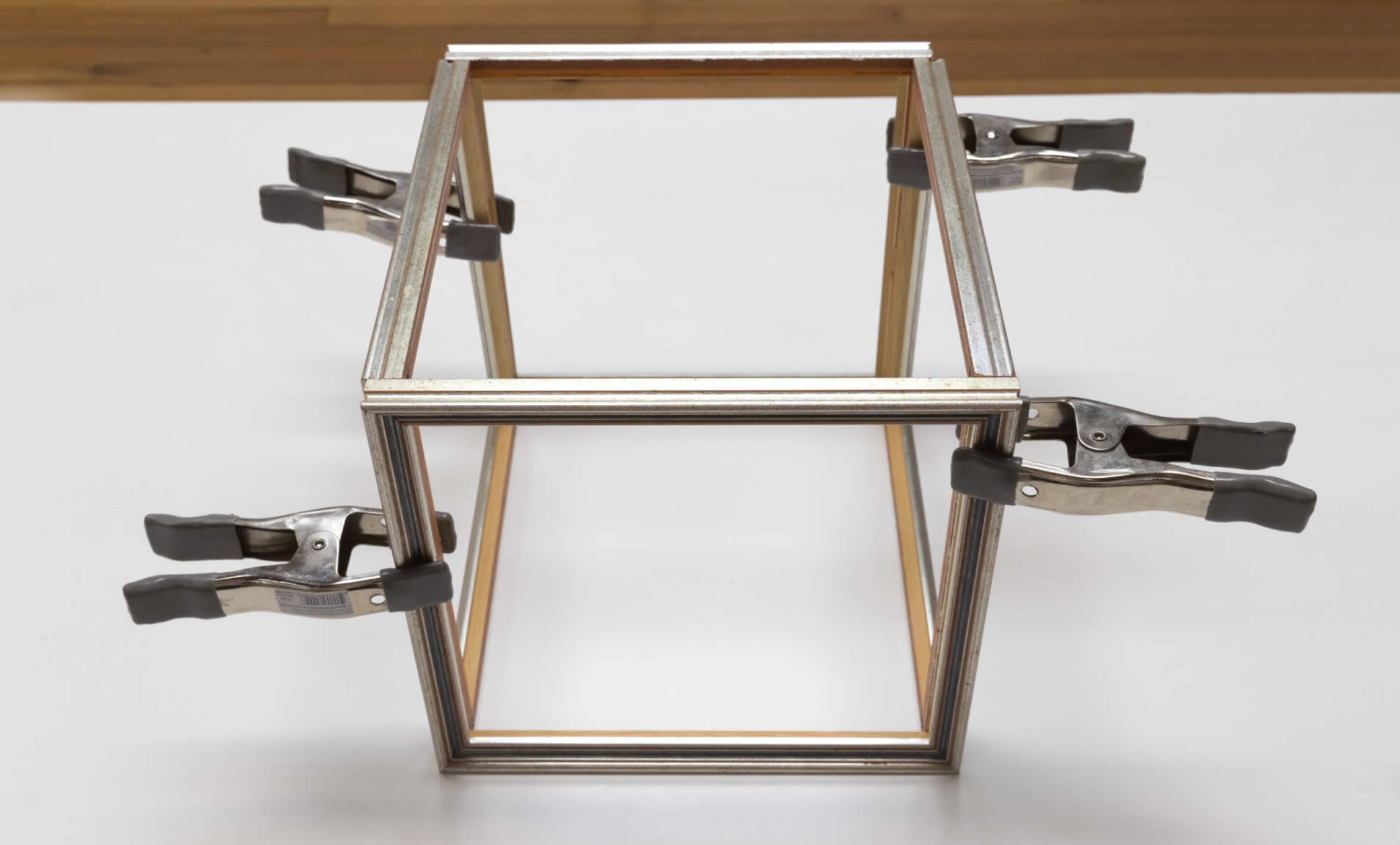 Step 2a of creating mini indoor greenhouse - clamp 4 of the frames together in the shape of a cube