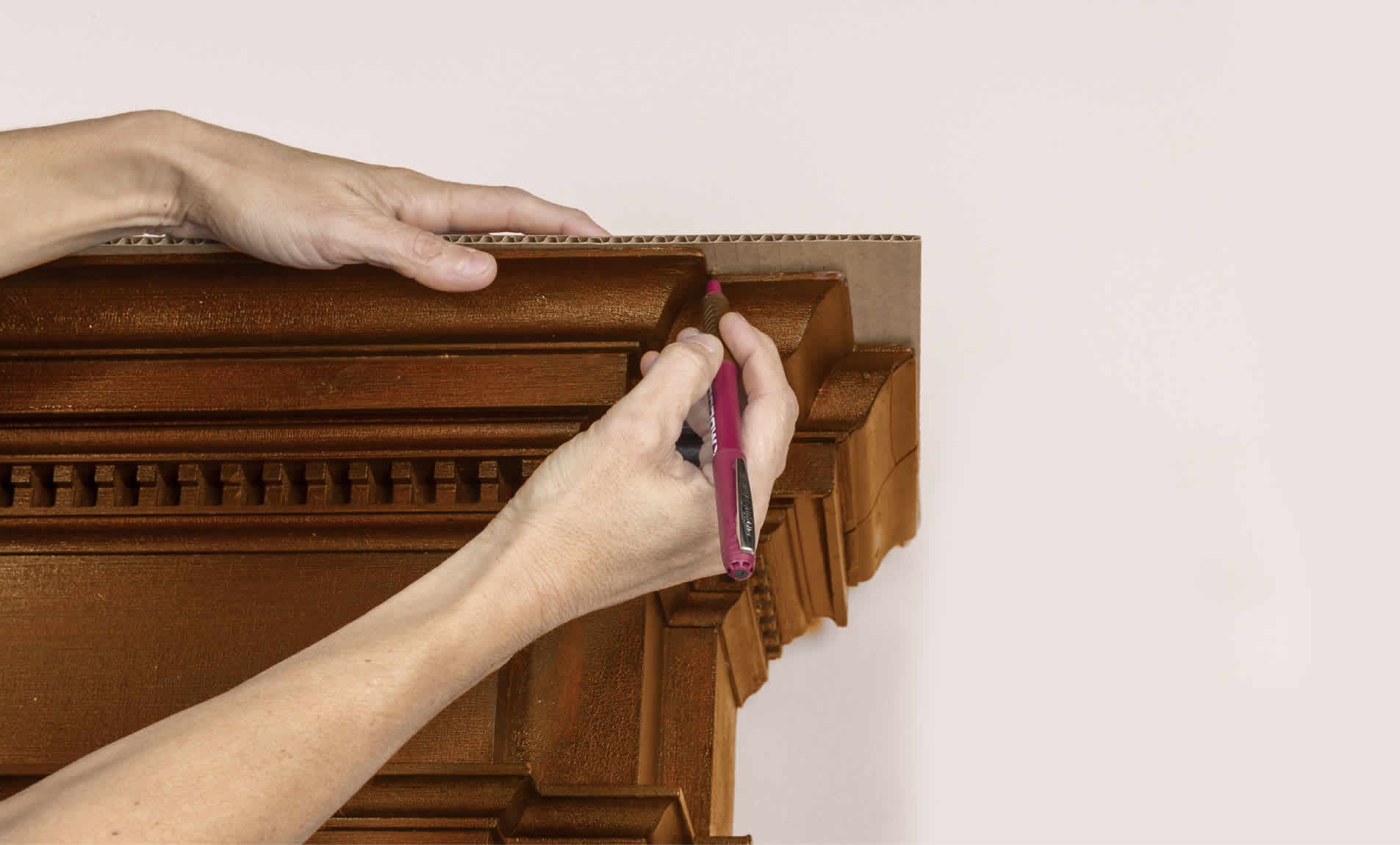 tracing cardboard around a fireplace mantel